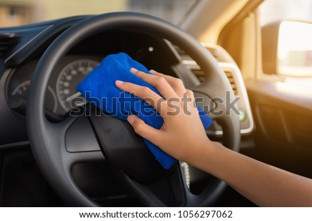 Close-up portrait of woman hand cleaning car steering wheel with microfiber towel.