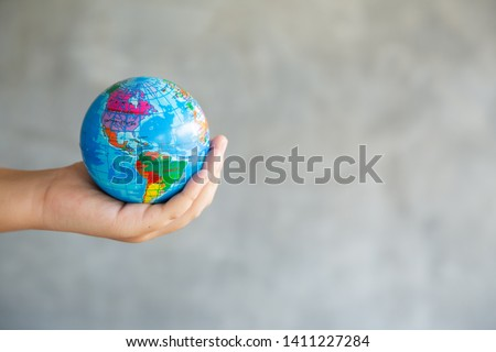 Close-up Portrait of Woman is Holding Global in Her Hands on gray Background. Save The Planet and Traveling Conceptual. Save The Earth and Care Environment Concept. #1411227284