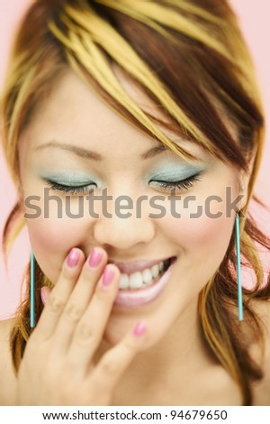 Close up portrait of woman laughing with hand over mouth