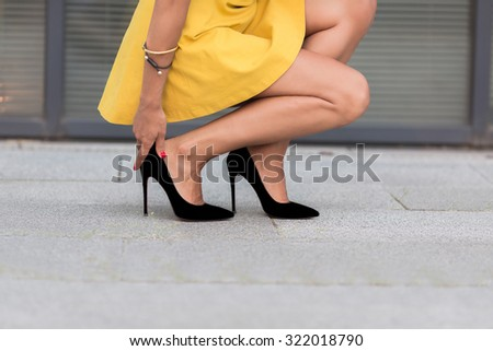 Close-up portrait of woman\'s legs on high heels. Lady in yellow dress sitting and touching her right leg near office building.