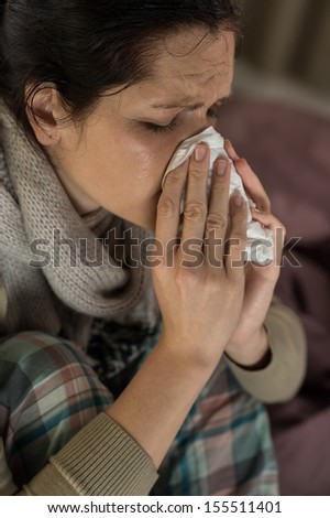 Close up portrait of woman sneezing into tissue