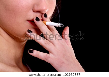Close-up portrait of woman with cigarette over black