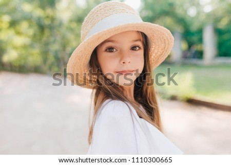 Close-up portrait of wonderful child with shiny brown eyes looking to camera with interest. Enthusiastic little girl in vintage straw hat decorated with ribbon posing during game in park.