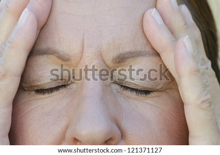 Close Up portrait of worried woman with closed eyes and hands on forehead.