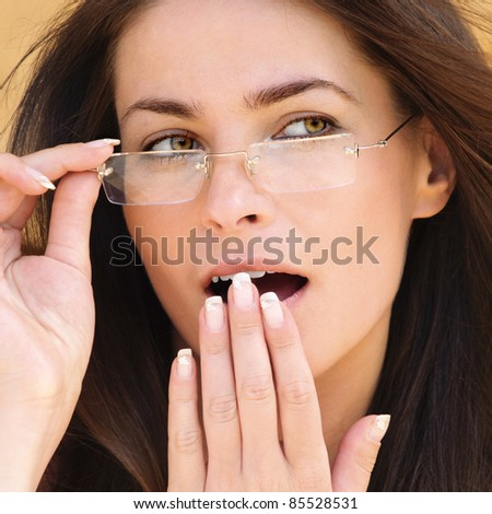 Close-up portrait of young amazed brunette woman wearing glasses against yellow background. - stock photo