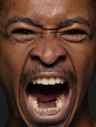 Close up portrait of young and emotional african-american man. Highly detail photoshot of male model with well-kept skin and bright facial expression. Concept of human emotions. Angry screaming.