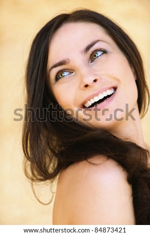 Close-up portrait of young attractive brunette smiling woman looking somewhere against yellow background.