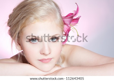 Close-up portrait of young beautiful blond girl with pink make-up over gray