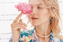 Close up portrait of young beautiful blonde woman hides her eye by peony flower, wearing trendy earrings, many rings, pearl, chain necklace, summer dress. Copy, empty space for text