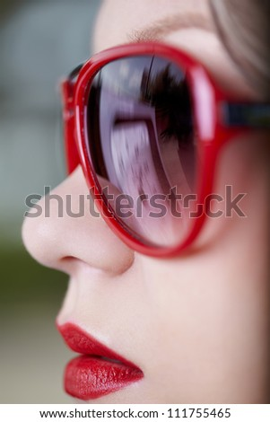 close-up portrait of young beautiful blonde woman. petrol pump is reflecting in sun-glasses - stock photo