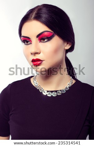 Close up  portrait of young beautiful  brown-eyed  woman with long black hair on white background. Arab woman. Scarlet makeup and black arrows. Fashion model shooting. Silver jewelry.