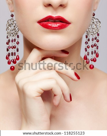 close-up portrait of young beautiful brunette woman in ear-rings touching her chin with manicured fingers - stock photo