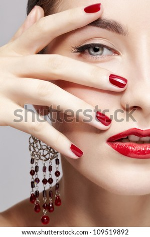 close-up portrait of young beautiful brunette woman in ear-rings touching her face with manicured hand