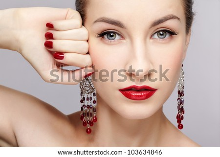 close-up portrait of young beautiful brunette woman in ear-rings touching her temple with manicured hand