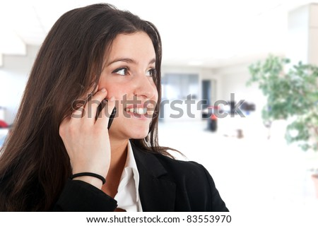 Close-up portrait of young beautiful business woman using her cell phone