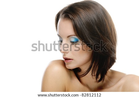 Close-up portrait of young beautiful dark-haired woman looking somewhere down against white background.