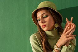 Close up portrait of young beautiful fashionable woman with green eyeshadow makeup, wearing turtleneck, trendy bucket hat, wrist watch, posing on mint color background. Copy, empty space for text