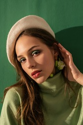 Close up portrait of young beautiful fashionable woman with green mono eyeshadow makeup, wearing turtleneck, trendy white beret, posing on bright mint color background