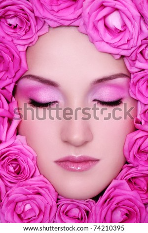 Close-up portrait of young beautiful fresh girl with pink make-up and bright roses around her face