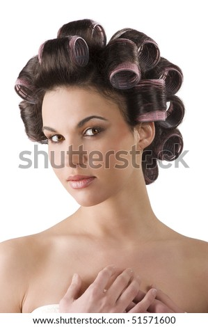 close up portrait of Young beautiful girl having hair curlers on her head isolated on white background