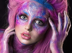 close up  portrait of young beautiful girl with colorful face painting. Halloween professional makeup. hair in paint. beauty portrait. pink and purple hair