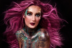 close up  portrait of young beautiful girl with colorful face painting. professional makeup. hair in paint. beauty portrait. pink flying hair