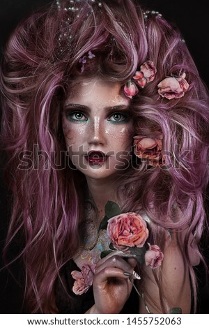close up portrait of young beautiful girl with flower professional makeup. elf princess with flower crown on head.  bright face art. spring fairy of flowers. lush pink hairdo with roses.