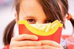 Close up portrait of young beautiful girl with french fries. Unhealthy fast food and calorie food. Horizontal image.