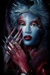 close up  portrait of young beautiful girl with Halloween professional colorful makeup. lush hairstyle in paint. nail art