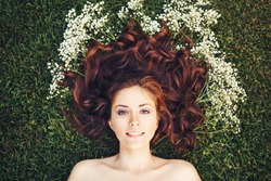 Close up portrait of young beautiful girl woman with red brown hair lying on grass with white small flowers around her head .View from above top overhead. Concept of spring summer youth happiness