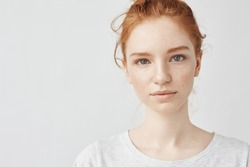 Close up portrait of young beautiful redhead girl in white shirt smiling looking at camera. Copy space. Isolated on white background.
