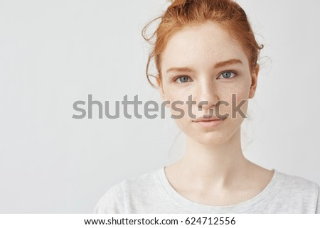 Close up portrait of young beautiful redhead girl in white shirt smiling looking at camera. Copy space. Isolated on white background. #624712556