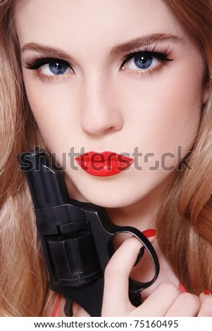 Close-up portrait of young beautiful sexy blond woman with revolver in hand