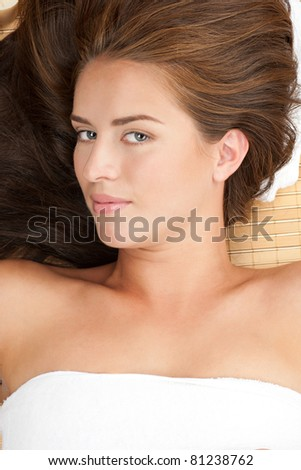 Close-up portrait of young beautiful spa woman lying on bamboo mat at spa salon