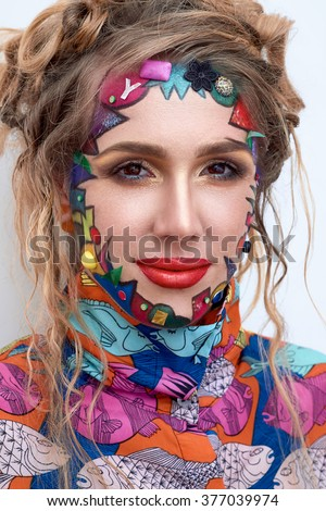 Close up portrait of young beautiful woman, model,  clown. Bright creative fantasy makeup, geometric shapes, circles. Multicolored paint, red, blue, orange, yellow, pink. Pop art style, avant garde.