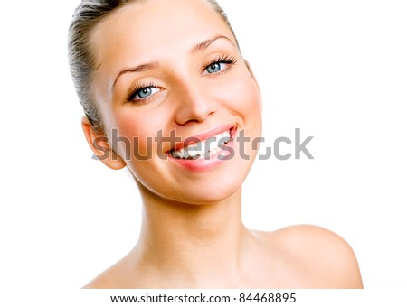 Close-up portrait of young beautiful woman's face with happy cheerful smile on it - white background