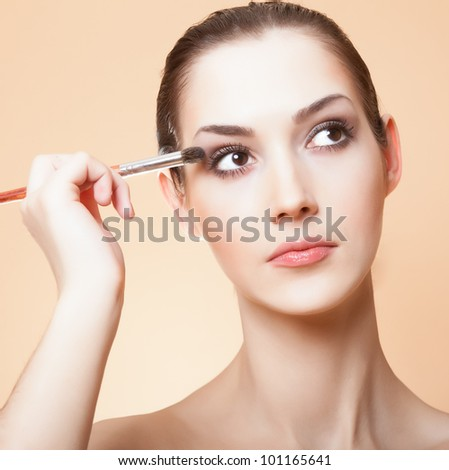 Close-up portrait of young beautiful woman with brush for make-up.
