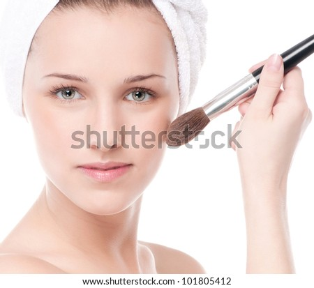 Close-up portrait of young beautiful woman with brush for make-up. Cheek zone