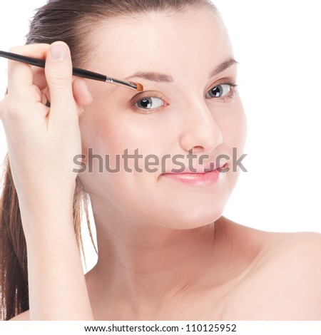 Close-up portrait of young beautiful woman with brush for make-up. Eye shadow zone