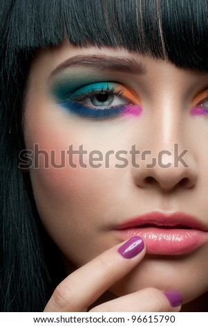 Close-up portrait of young beautiful woman with colorful stylish make-up and manicure