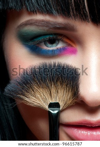 Close-up portrait of young beautiful woman with colorful stylish make-up and with brush for makeup