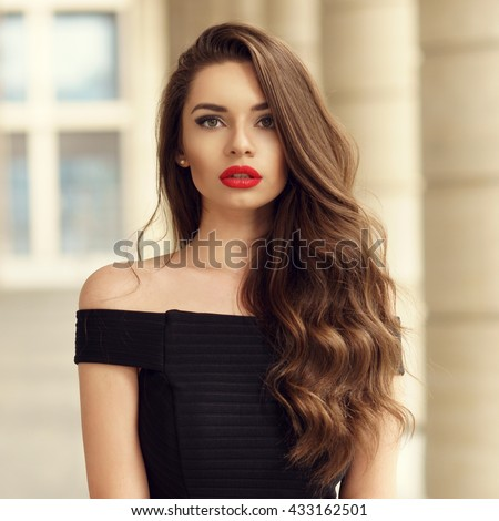 Close up portrait of young beautiful woman with long brunette curly hair posing against architectural background and looking at you