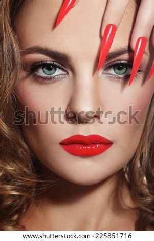 Close-up portrait of young beautiful woman with red lipstick and long stiletto nails