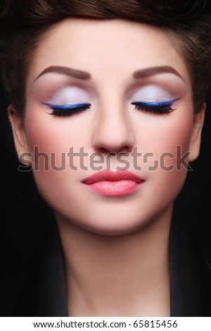 Close-up portrait of young beautiful woman with stylish make-up and closed-eyes