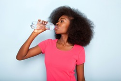Close up portrait of young black woman drinking bottle of water