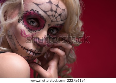 Close-up portrait of young blond girl with sad face with Calaveras makeup upset looking at the camera while holding her hands near face isolated on red background with copy place