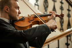 close-up portrait of young caucasian man playing violin, professional violinist perform music, practicing
