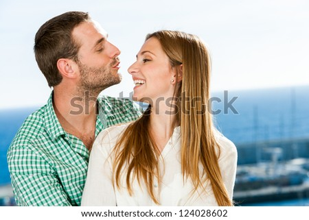 Close up portrait of young couple playing around outdoors.