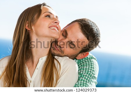 Close up portrait of young couple sharing secrets outdoors.