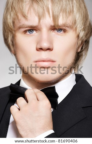 Close-up portrait of young fashion man in evening gentleman style with bow-tie and black suit